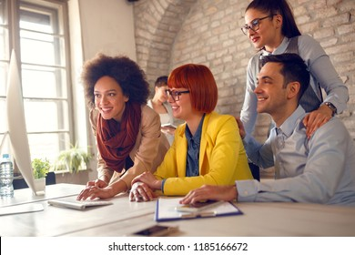 Cheerful young employees working together on computer