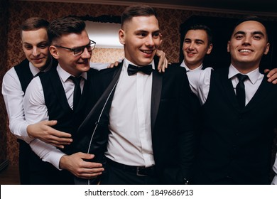 Cheerful, young, energetic witnesses of the groom next to the groom. Friends congratulate the groom.