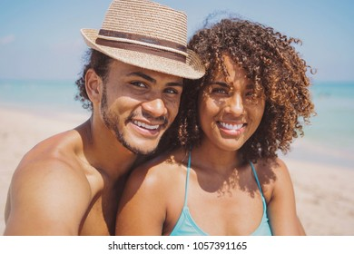 Cheerful young ethnic man and woman embracing and smiling while looking at camera on sandy beach at the sea.