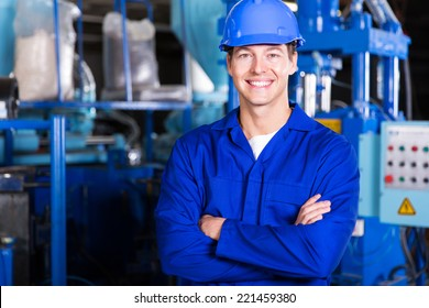 cheerful young factory worker with arms crossed
