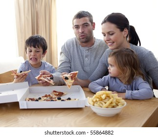 Cheerful young family eating a pizza in the living-room at home