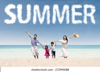 Cheerful young family enjoy holiday on the tropical seaside under a summer's cloud