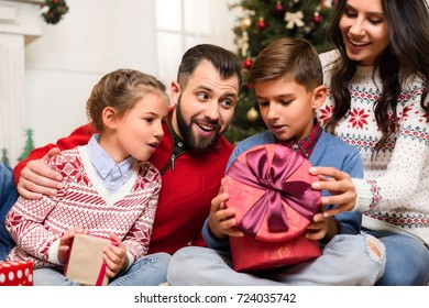 cheerful young family opening christmas presents together at home