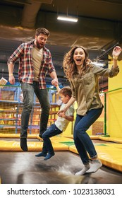 Cheerful young family with their little son jumping on a trampoline together at the entertainment centre