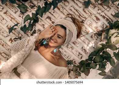 cheerful young fashionable woman in turban outdoors at sunset