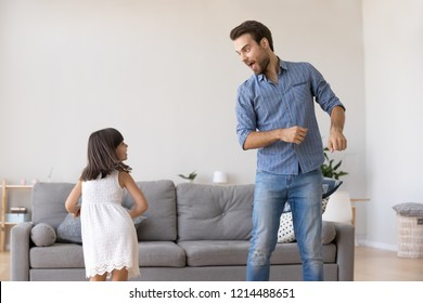 Cheerful young father and little daughter standing in living room at home moving dancing to favourite song together. Child having fun with loving daddy. Active lifestyle leisure activities concept