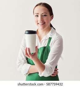 Cheerful young female barista in green apron, holding a paper to-go cup of coffee