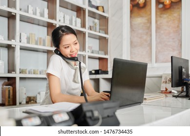 Cheerful young female beauty salon receptionist talking on phone with clients and writing down information apout appointments