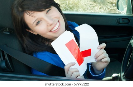 Cheerful young female driver tearing up her L sign sitting in her car