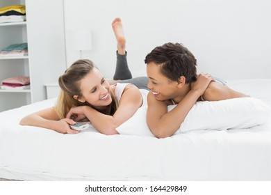 Cheerful young female friends with remote control lying in bed at home