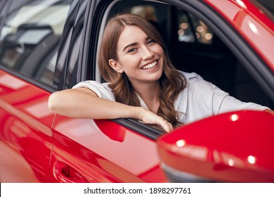 Cheerful young female sitting in shiny red car on passenger seat and looking out open window while enjoying purchase in dealership