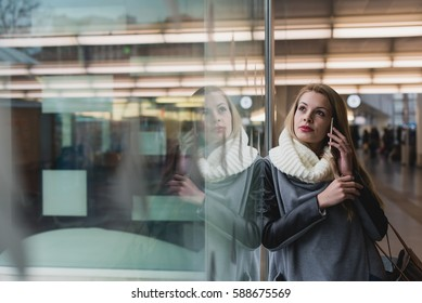 Cheerful young female talking with phone the airport building. Horizontal indoors shot.