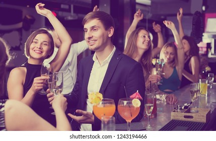 Cheerful young females and males celebrating corporate in the bar at night