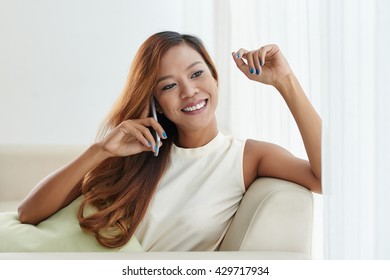 Cheerful young Filipino woman sitting on sofa and chatting on phone