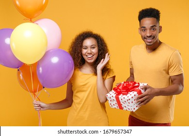 Cheerful young friends couple african american guy girl isolated on yellow background. Birthday holiday party concept. Celebrate hold colorful air balloons white red present box with gift ribbon bow