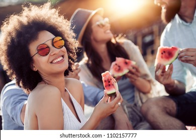 Cheerful young friends eating watermelon on beach,having fun together.
