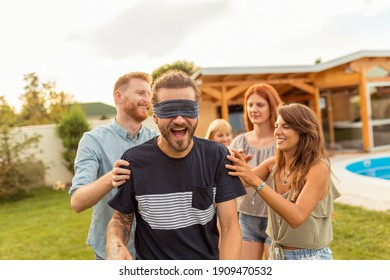 Cheerful young friends having fun at poolside summertime outdoor party, playing blind man's buff, running and chasing each other on the backyard lawn