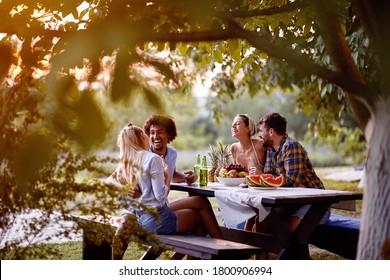 fröhliche junge Freunde, die auf der Party im Freien sitzen, sprechen und lachen und Freundschaft genießen.