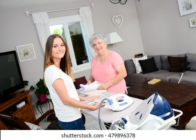 cheerful young girl ironing and helping with household chores an elderly woman at home