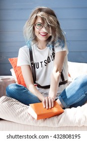 Cheerful young girl student with fancy tousled hairstyle and round glasses. She smiles sincerely. She is resting on the balcony, on the sofa with orange pillows. She smiles brightly. Sunny summer day.