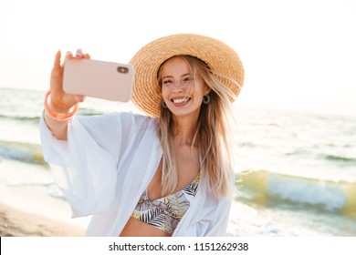 Cheerful young girl in summer hat and swimwear spending time at the beach, taking a selfie with outsretched hand