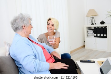 cheerful young girl taking care of an old senior woman at home and handing a glass of water