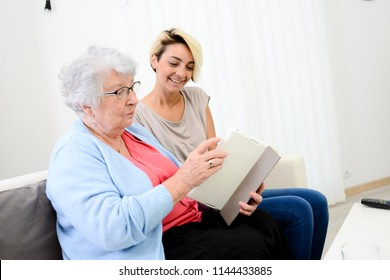 cheerful young girl taking care of an elderly woman at home