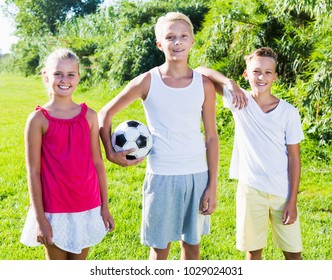 Cheerful young girl with two friends after game with ball outdoors