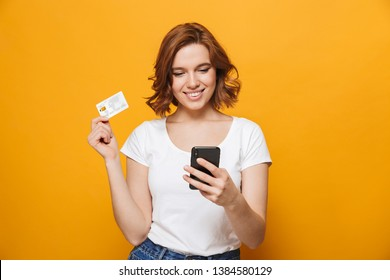 Cheerful young girl wearing t-shirt standing isolated over yellow background, using mobile phone, showing plastic credit card