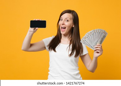 Cheerful young girl in white clothes hold mobile phone with blank empty screen fan of cash money in dollar banknotes isolated on yellow orange background. People lifestyle concept. Mock up copy space
