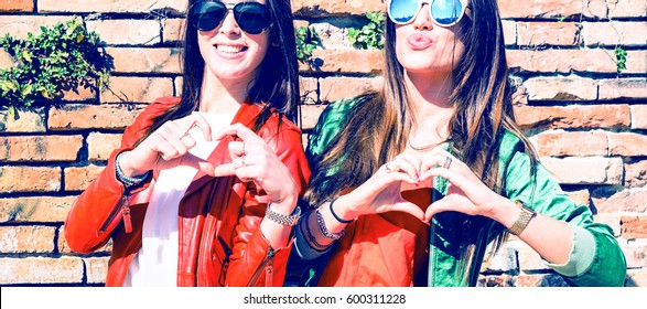 Cheerful young girlfriends having fun making heart shape next to old city wall - Happy smiling teen women doing hearts with hands outdoors - Joyful  female friends love gesture - Concept of friendship