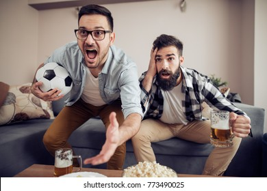 Cheerful young guys are watching match on couch at home and drink beer.