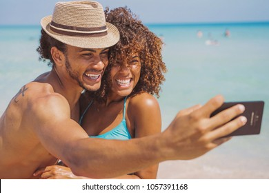 Cheerful young happy ethnic man and woman standing on sunny sandy beach and taking selfie together.