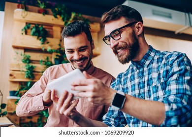 Cheerful young hipster guys having fun watching funny videos from social networks via touchpad together, smiling bearded man showing his results to friend playing online games on portable pc
