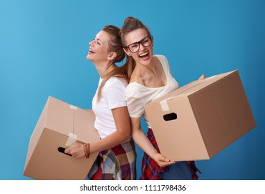 cheerful young hipster roommates in white shirts with a cardboard boxes and standing back to back isolated on blue