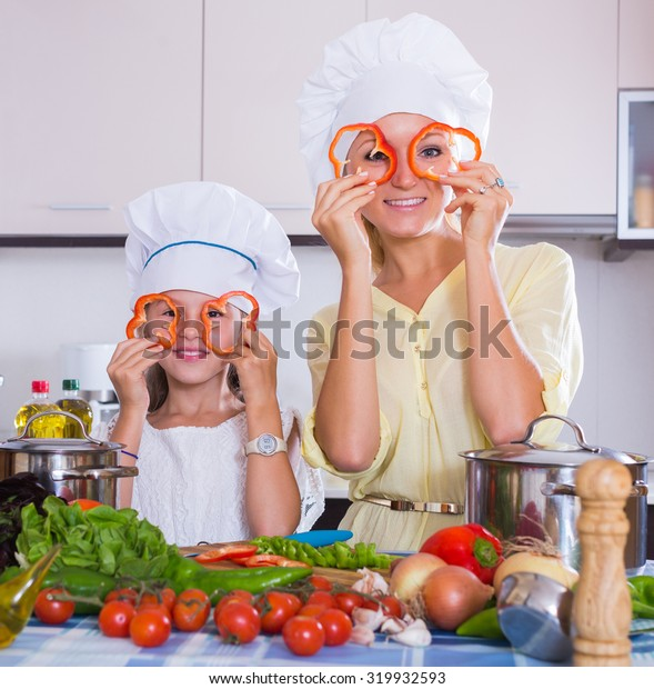 Cheerful young housewife and her daughter with veggies at kitchen table