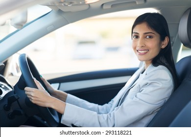 cheerful young indian businesswoman driving a car