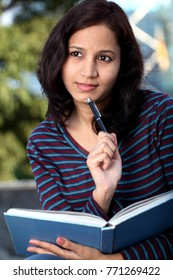 Cheerful young indian college student outdoors