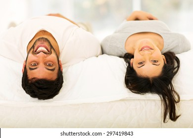 cheerful young indian couple lying on bed looking at the camera