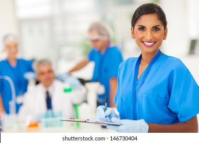 cheerful young indian medical researcher writing report in the lab
