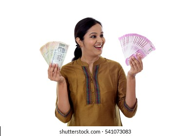 Cheerful young Indian woman holding currency notes