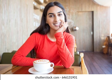 Cheerful young Indian woman sitting in cafe