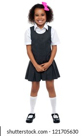Cheerful young kid in pinafore dress posing smilingly isolated on white background.