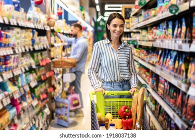 Cheerful Young Lady Doing Shopping Buying Groceries In Supermarket Standing And Pushing Trolley Cart Full Of Healhty Food, Smiling Woman Choosing Products And Looking At Shelf Indoors