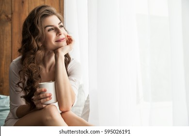 Cheerful young lady holding white mug and looking at window. Horizontal indoors shot.