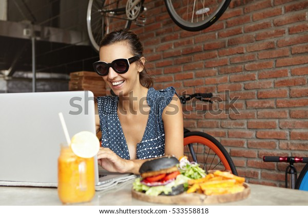 Cheerful young lady in shades sitting in front of laptop computer, looking at screen and smiling while posting photos via social networks. Female student using notebook pc during lunch break