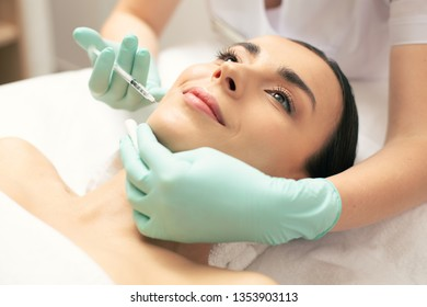Cheerful young lady smiling while professional cosmetologist making injection into her facial skin