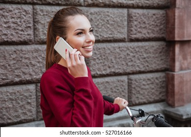Cheerful young lady walking with her bicycle in the city while standing near wall and talking by her phone. Look aside.