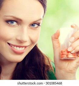 Cheerful young lovely brunette woman showing bottle with pills, outdoor