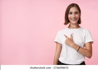Cheerful young lovely short haired brunette female with natural makeup smiling happily while pointing aside with forefinger, isolated over pink background